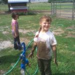 Mud is just another toy for kids on the farm.