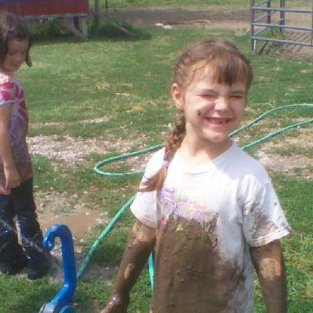 Two girls playing is mud on farm